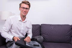 Young smiling business man packing his bag on couch Stock Image