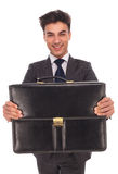 Young smiling business man  showing a briefcase Stock Image