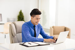 Young smiling business man  working in office Royalty Free Stock Images