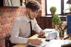 Young smiling business man writting with pen on paper sheet at working place royalty free stock image