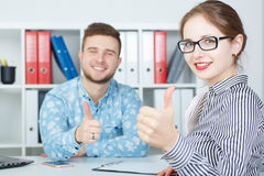 Young smiling business partners showing OK sign with thumbs up. Royalty Free Stock Photos