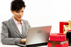 Young smiling business woman. Young smiling business women with laptop and gifts Royalty Free Stock Photo