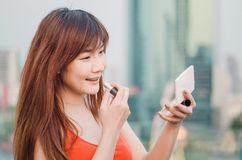Young smiling business woman drawing lips with lipstick standing outdoors over city. Background royalty free stock photos