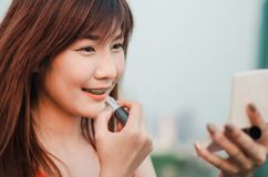Young smiling business woman drawing lips with lipstick standing outdoors over city. Background stock image