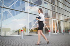Young and smiling business woman. Goes at the airport with a note-book in her hands Royalty Free Stock Image