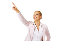 Young smiling business woman pointing for copyspace or something Stock Images