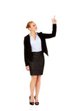 Young smiling business woman pointing up Stock Photography