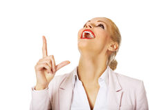 Young smiling business woman pointing up Royalty Free Stock Images