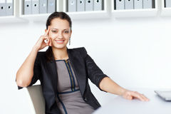 Young smiling business woman sitting at the desk Royalty Free Stock Photos