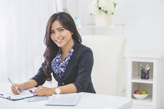 Young smiling business woman working on her paperwork Royalty Free Stock Images