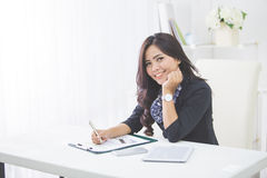 Young smiling business woman working on her paperwork Stock Images