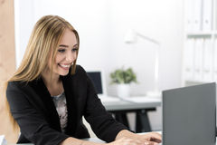 Young smiling business woman working at laptop in the office. Businesswoman chatting with someone online royalty free stock photo
