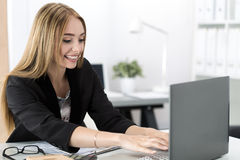 Young smiling business woman working at laptop in the office. Businesswoman chatting with someone online stock image