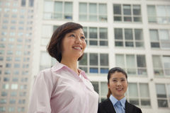 Young smiling business women standing outside of CBD, portrait Royalty Free Stock Images