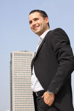 Young smiling businessman. In a black suit with modern office building on a background royalty free stock photo