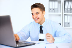 Young smiling businessman with cup of coffee in office. Portrait of young smiling businessman holding cup of coffee and using a laptop at his workplace in bright Stock Photos