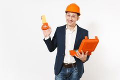 Young smiling businessman in dark suit, protective construction orange helmet holding opened case with instruments or. Toolbox and toy saw isolated on white stock image