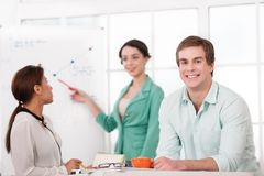 Young smiling businessman and his creative team Stock Photos