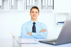 Young smiling businessman at his workplace in office Stock Images