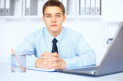Young smiling businessman at his workplace in office. Portrait of young smiling businessman at his workplace in bright office Royalty Free Stock Images