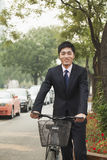 Young, smiling businessman holding a bicycle on a city street in Beijing, China Royalty Free Stock Images