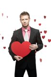 Young smiling businessman holding big red heart Royalty Free Stock Image