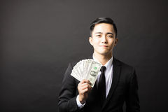 Young smiling businessman holding money Stock Image