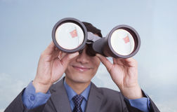 Young smiling businessman looking through binoculars, reflection of Chinese flag, Beijing, China Stock Photography