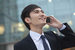Young smiling businessman on the phone looking up Stock Images