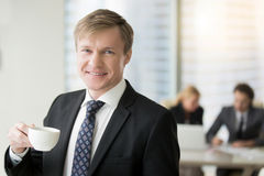 Young smiling businessman. Portrait of young successful friendly smiling businessman looking at camera, relaxing after meeting with cup of coffee, creative stock images