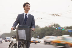 Young, smiling businessman riding a bicycle on the street with cars speeding by in Beijing, China royalty free stock image