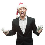 Young smiling businessman in santa hat holding money Stock Images
