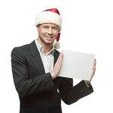 Young smiling businessman in santa hat holding sign Stock Photos