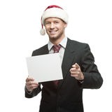 Young smiling businessman in santa hat holding sign Royalty Free Stock Photography