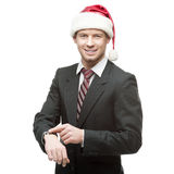 Young smiling businessman in santa hat pointing at watch Royalty Free Stock Image