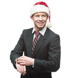 Young smiling businessman in santa hat pointing at watch Stock Photo