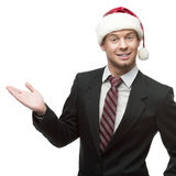 Young smiling businessman in santa hat showing empty space Royalty Free Stock Images
