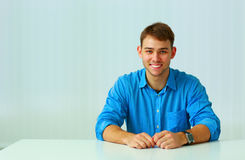 Young smiling businessman sitting at the table Stock Photos