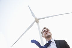 Young smiling businessman standing beside a wind turbine, tie is blowing in the wind Stock Photography