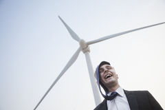Young smiling businessman standing beside a wind turbine, tie is on his head Royalty Free Stock Image