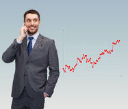 Young smiling businessman talking with smartphone. Business, technology, people and finances concept - young smiling businessman talking with smartphone over Royalty Free Stock Photos