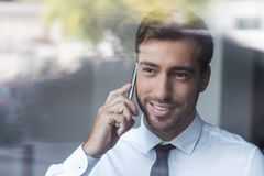 Young smiling businessman talking on smartphone and looking out royalty free stock photo