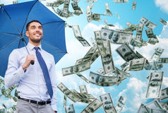 Young smiling businessman with umbrella outdoors. Business, economy, finances and people and concept - young smiling businessman with umbrella over blue sky and Stock Photography