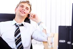 Young smiling businessman using cell phone Royalty Free Stock Photos