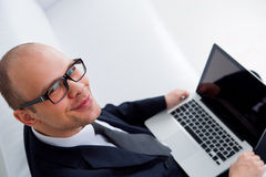 Young smiling businessman using laptop Royalty Free Stock Photography