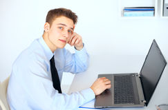Young smiling businessman working on laptop. Side view young smiling businessman working on laptop in bright office Royalty Free Stock Photos