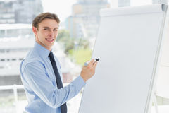 Young smiling businessman writing on whiteboard with marker Royalty Free Stock Photos