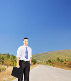 Young smiling businessperson holding a suitcase on a road Royalty Free Stock Photo