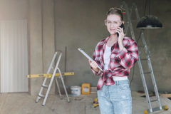 Young smiling businesswoman builder,engineer, architect,designer in construction glasses is standing in workshop. Talking on cell phone and holding clipboard Stock Photo