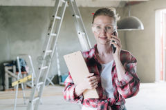 Young smiling businesswoman builder, engineer, architect, designer in construction glasses is standing. Talking on cell phone and holding a clipboard. In Stock Images